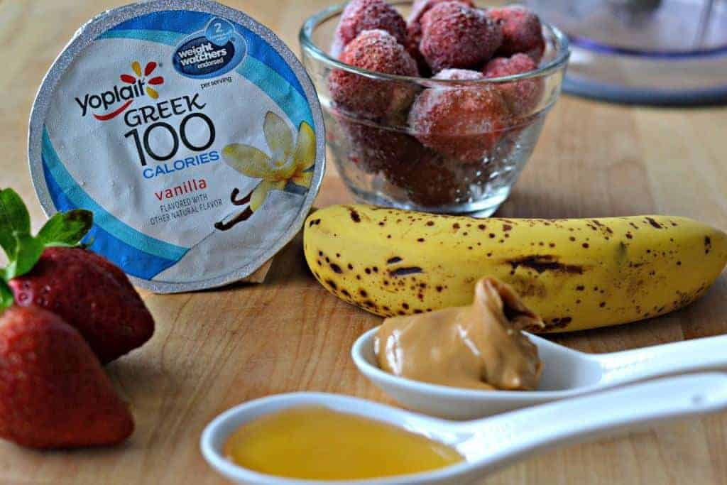 Yogurt, frozen strawberries, banana, and peanut butter for making a smoothie