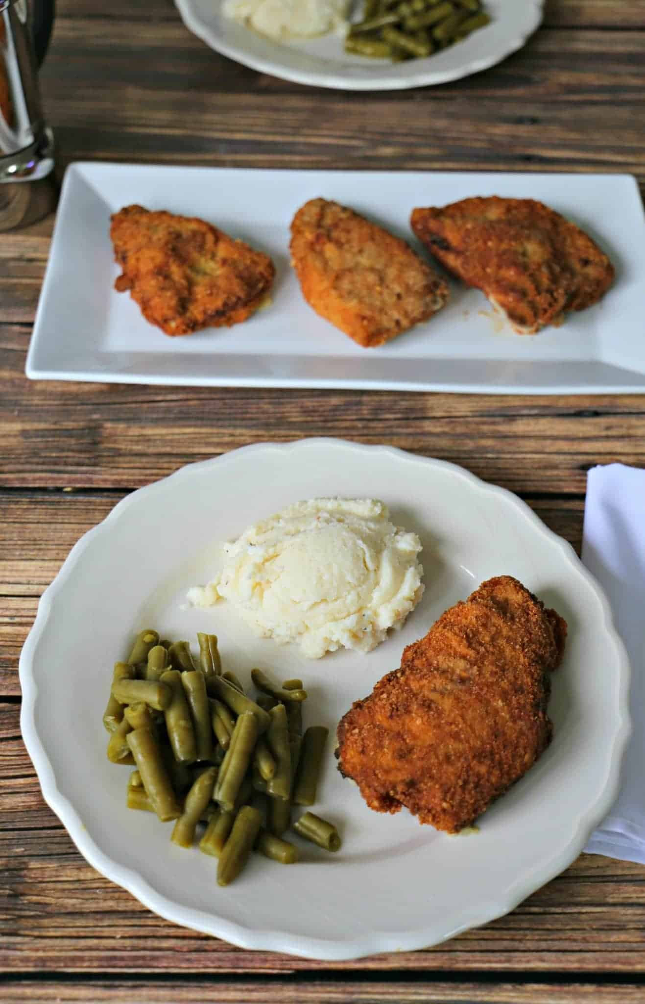 Pork Cordon Bleu on a plate with mashed potatoes and green beans