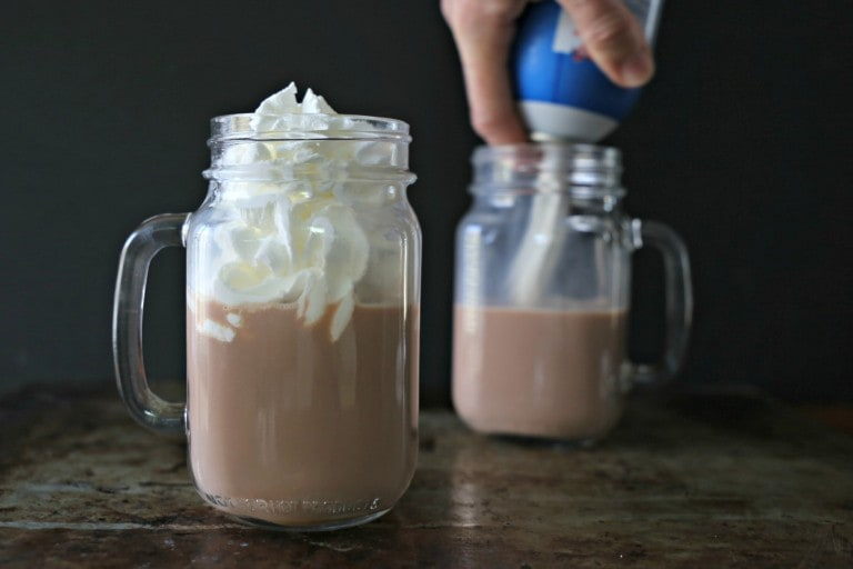 hot chocolate being topped with whipped cream