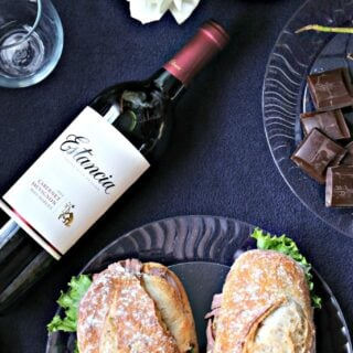 beef sandwich with horseradish spread and a bottle of wine
