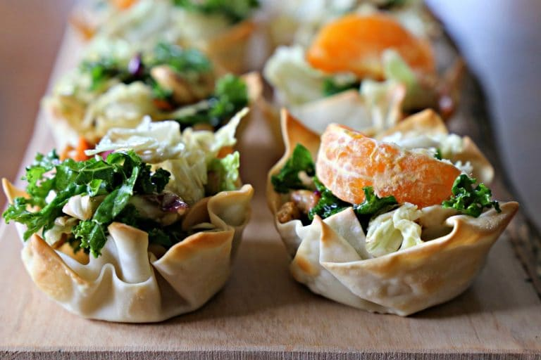 mini salad cups in wonton wrappers topped with orange slices
