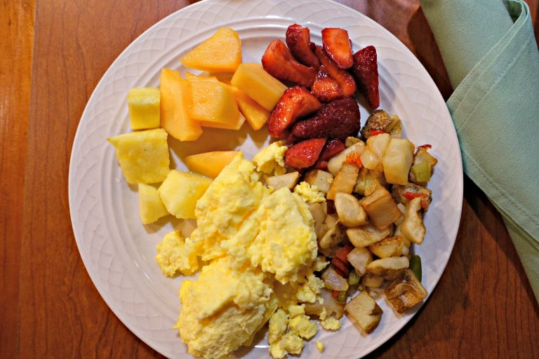 eggs, fruit, and potatoes on a plate