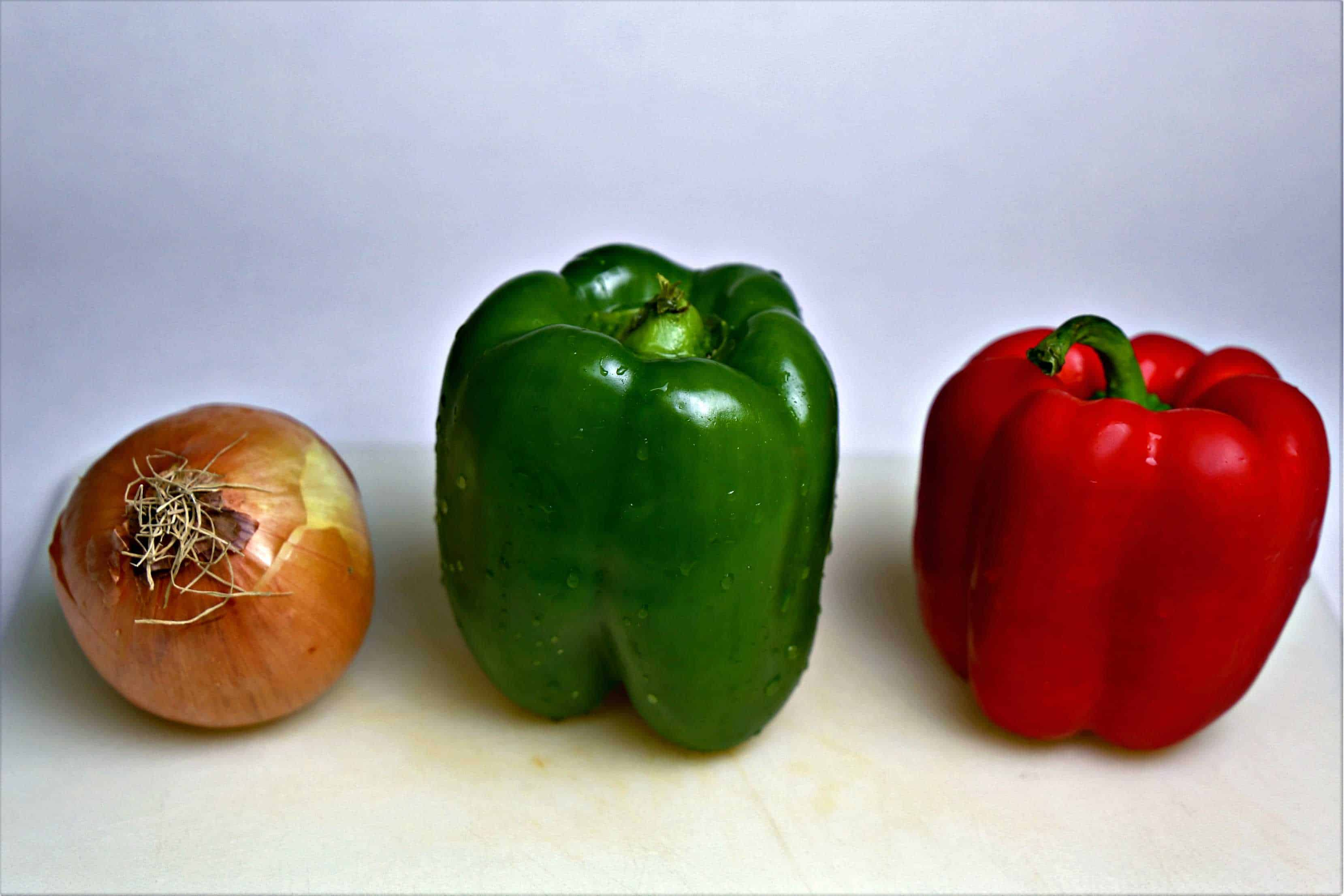 an onion, green bell pepper, and a red bell pepper