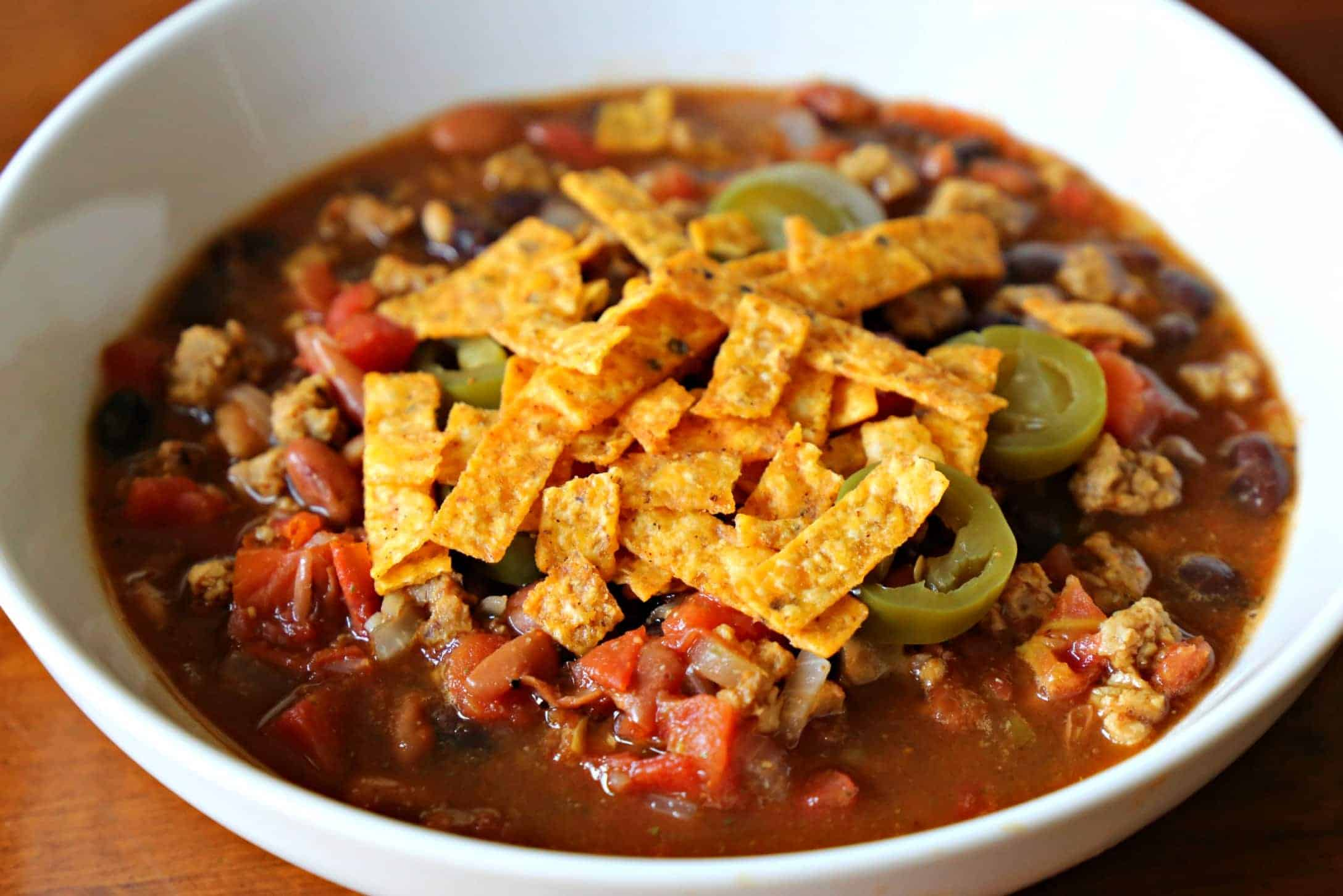 Bowl of taco soup with tortilla strips and jalapenos.