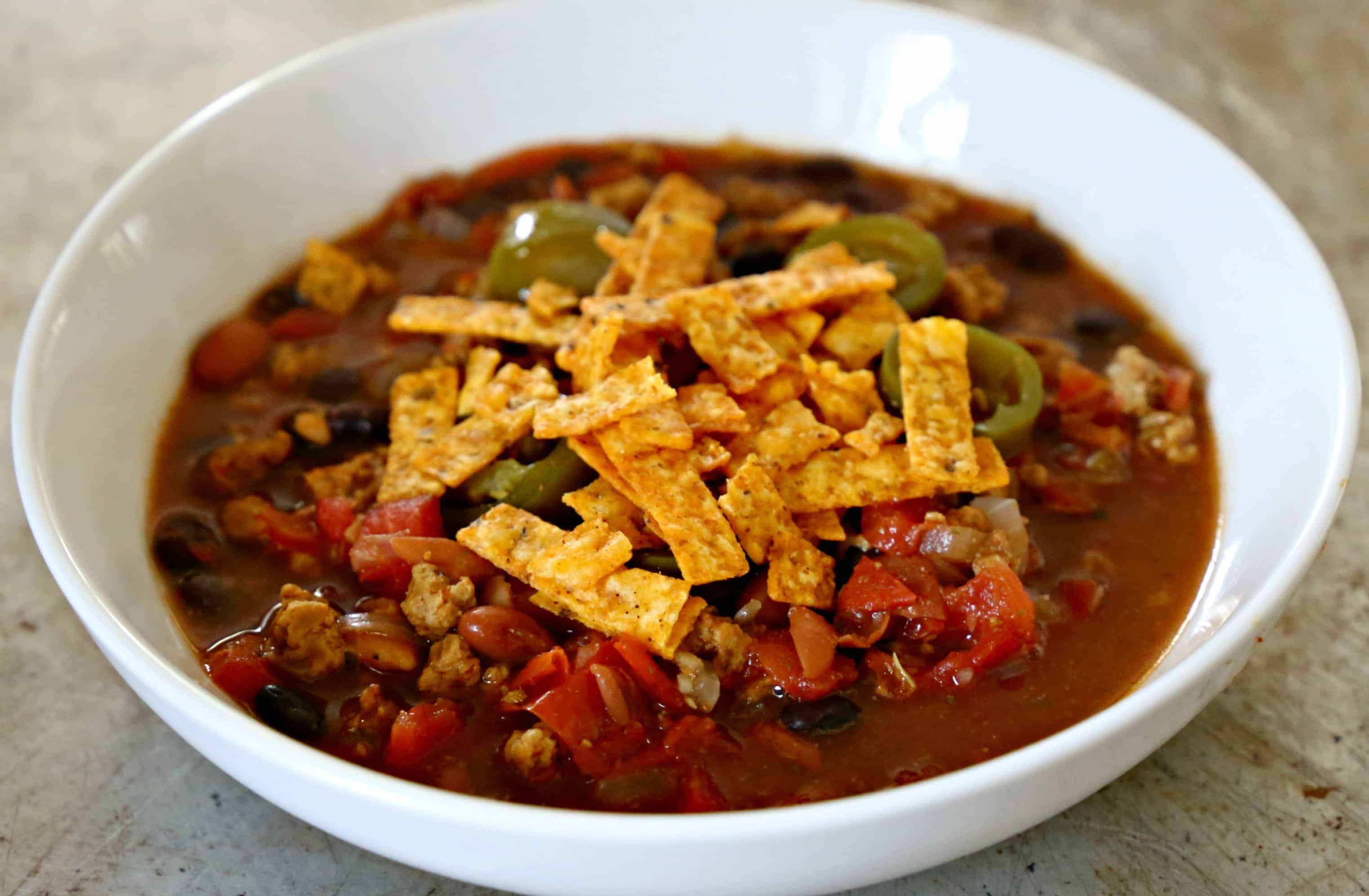 White bowl filled with taco soup topped with tortilla strips.