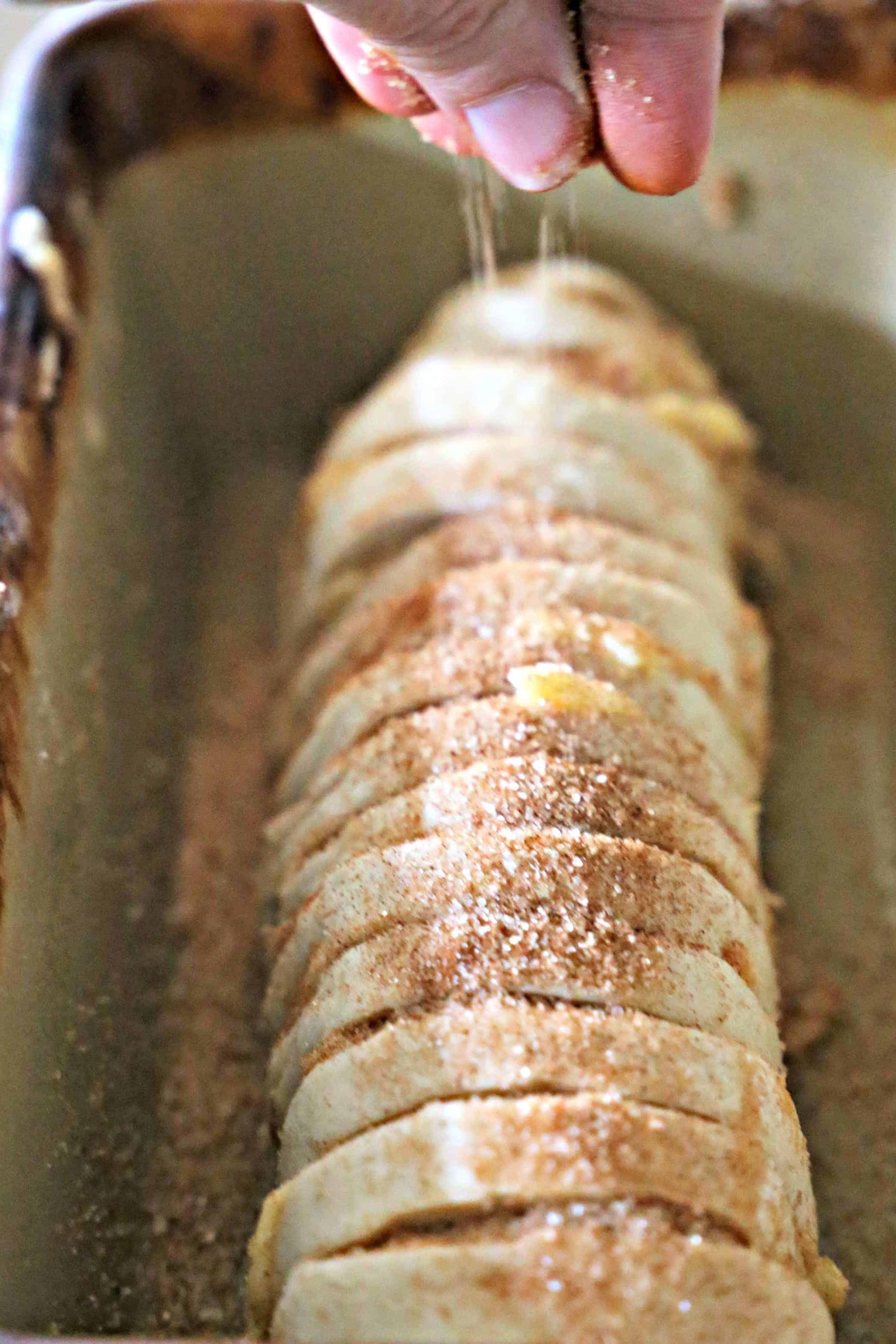 sprinkling sugar over loaf of bread