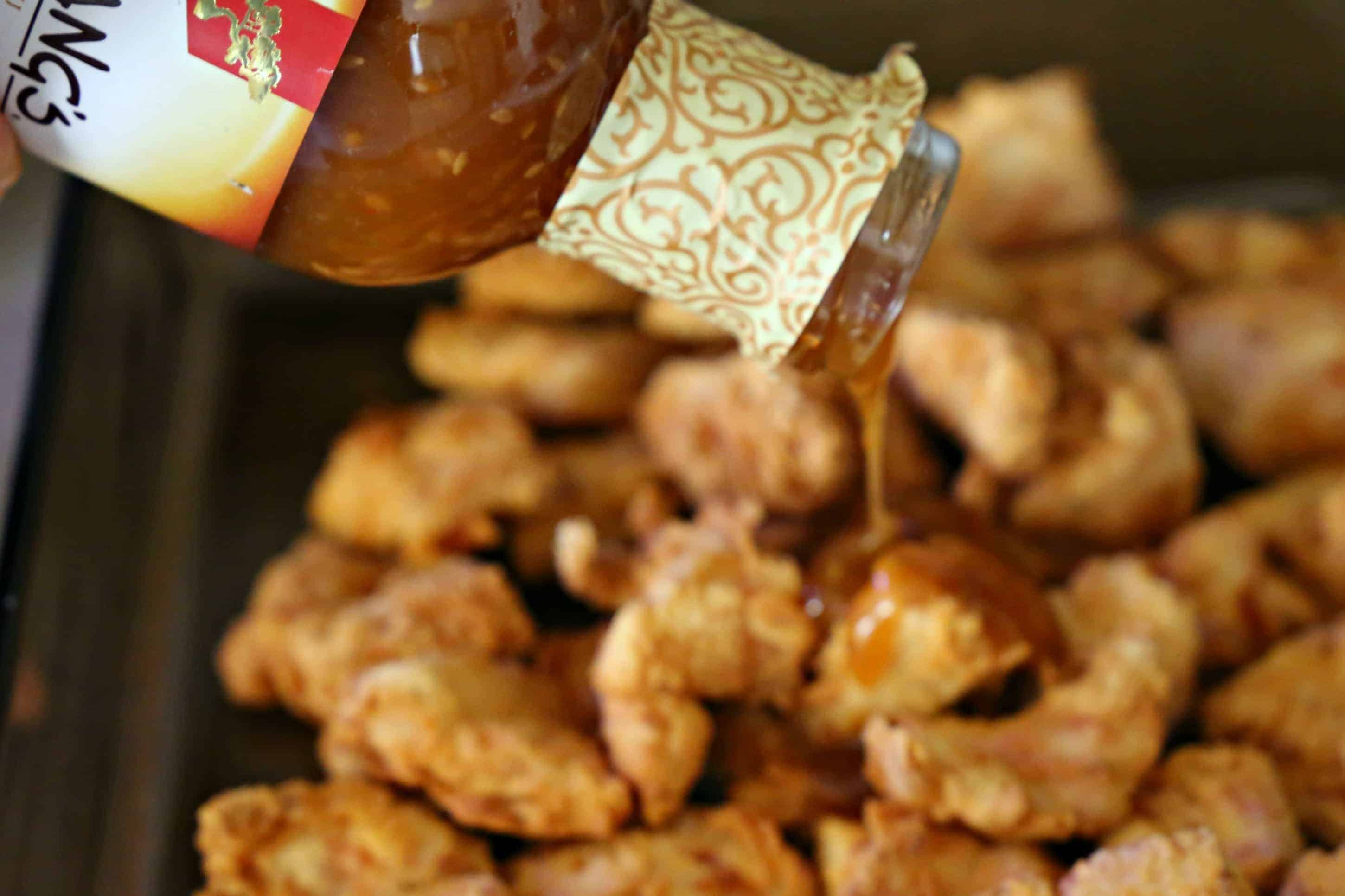 pouring sesame sauce over chicken nuggets