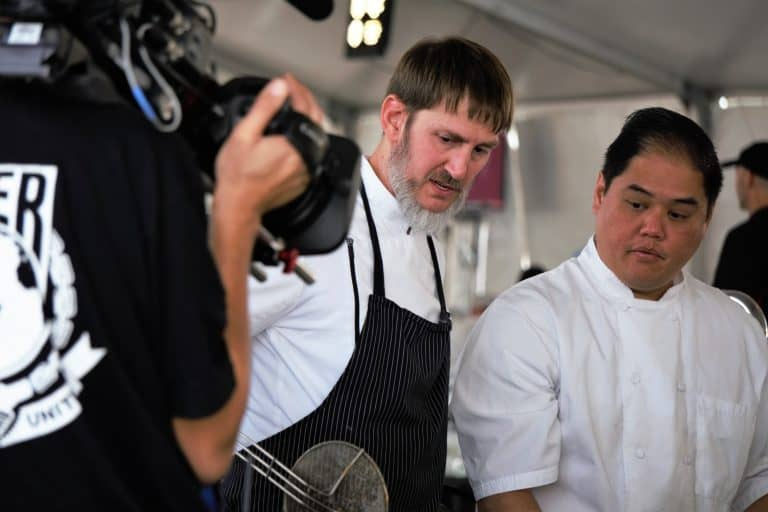 two men cooking and being filmed