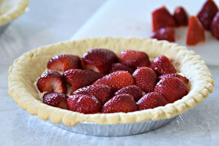 Pie crust with layer of cream cheese and topped with strawberries