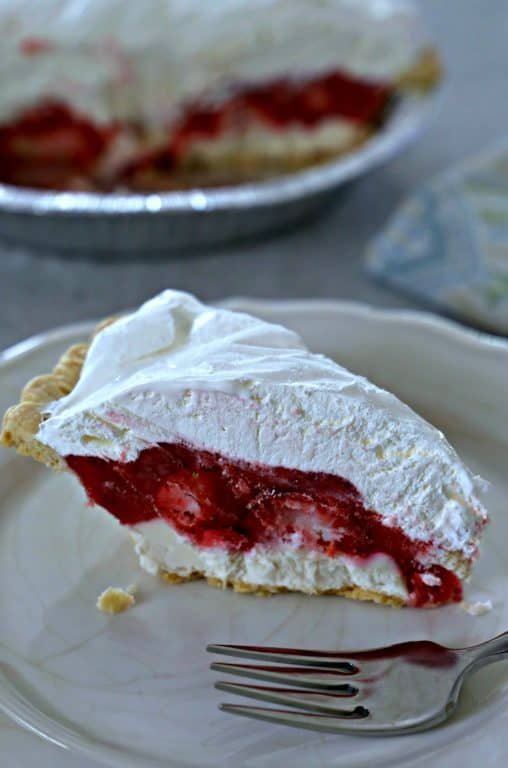 Slice of strawberry pie with a layer of cream cheese and topped with Cool Whip.