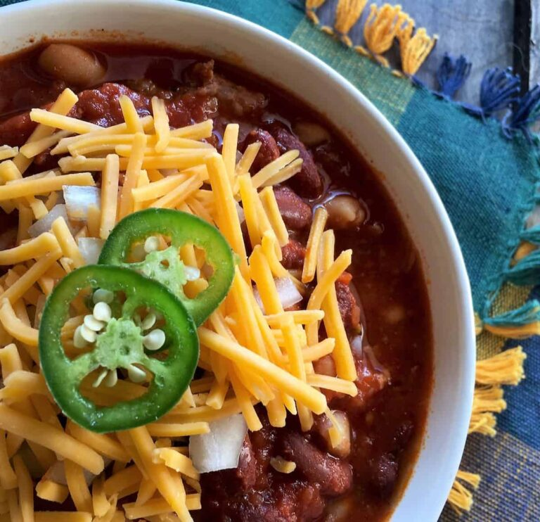 bowl of spicy chili with cheese, onions, and jalapenos on top