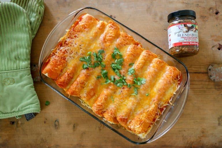 enchiladas on a board with a jar of BLENDABELLA