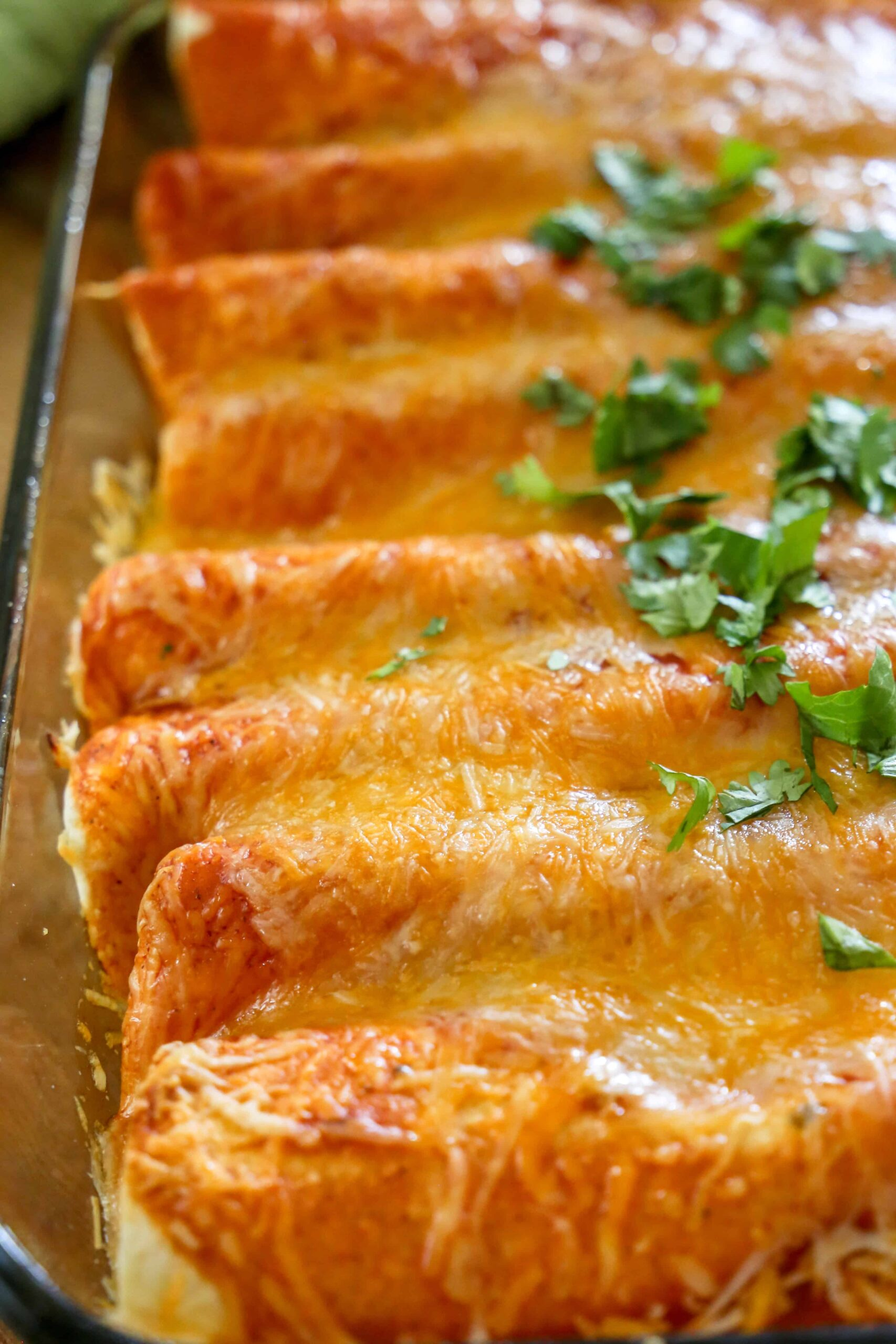 red enchiladas in a pan topped with cilantro