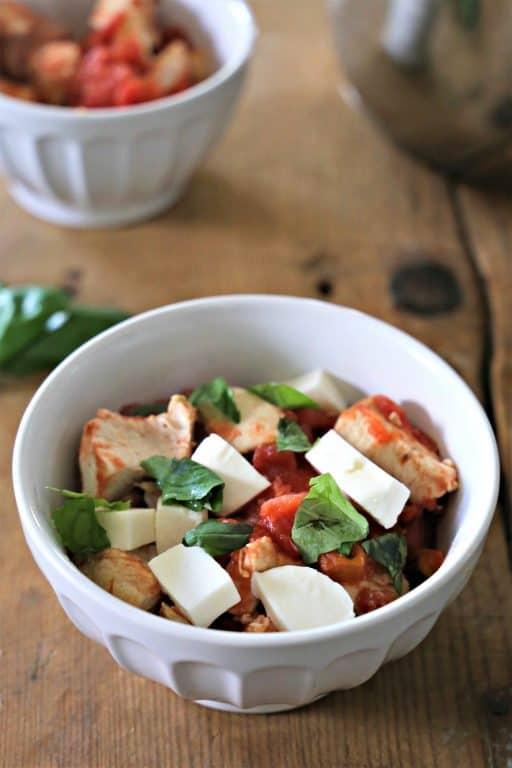 bowl of chicken, tomatoes, mozzarella cheese, and basil