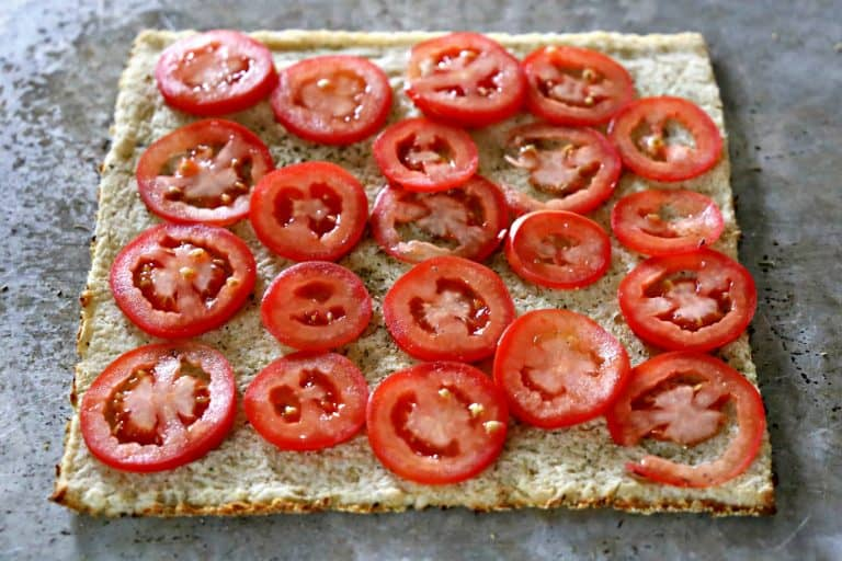 layer of tomatoes on a pizza crust