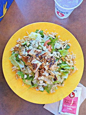 Yellow salad bowl with blackened chicken, cheese, and packet of salad dressing.