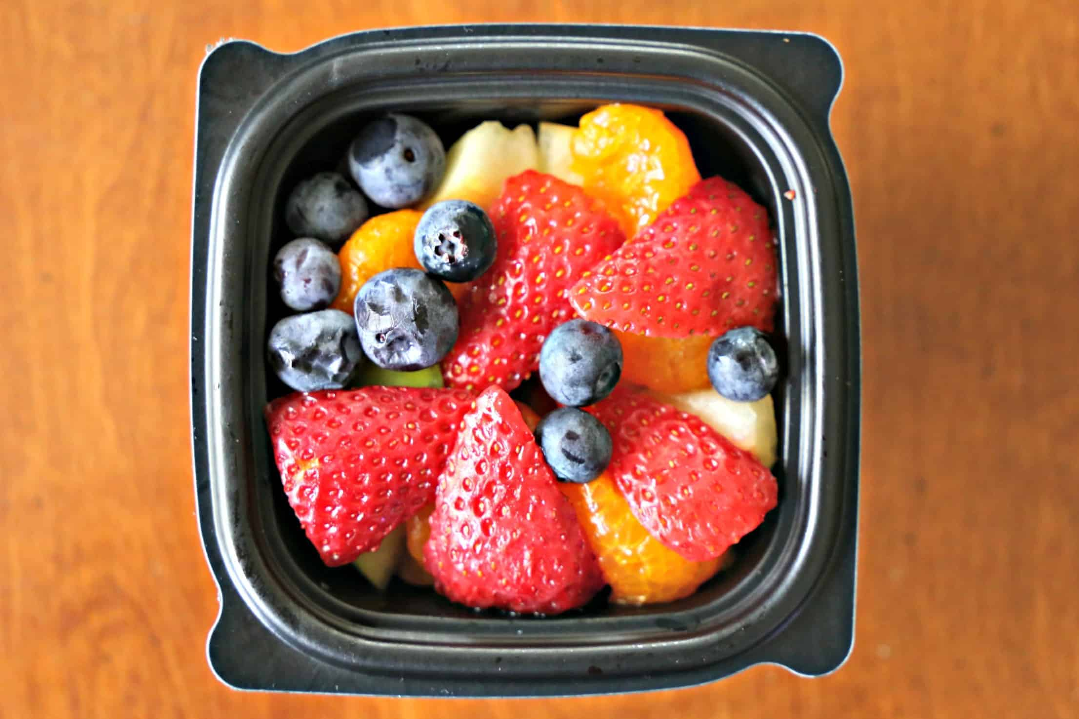 Small fruit cup with strawberries, mandarin segments, and blueberries.