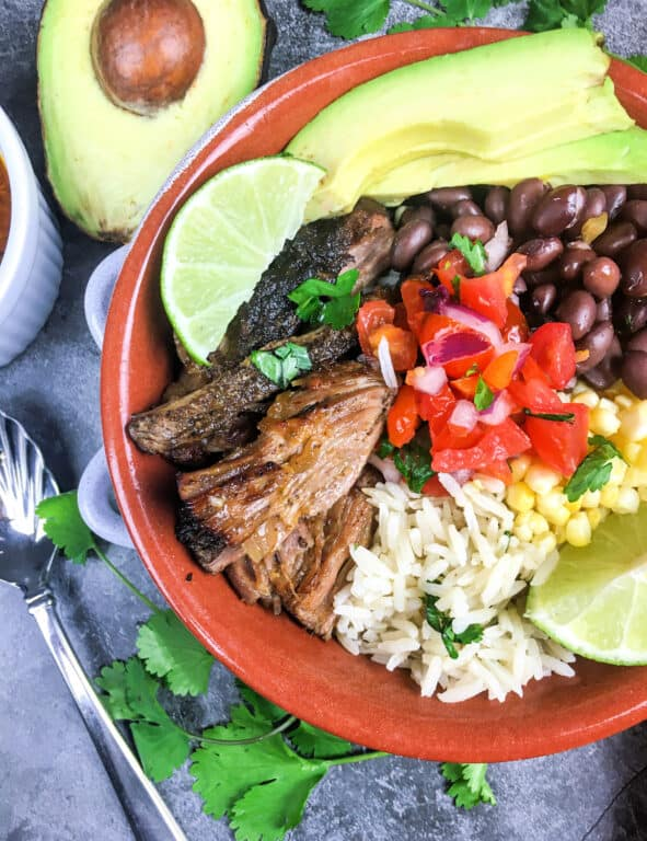 Carnitas Bowl with meat, rice, beans, tomatoes, and avocado
