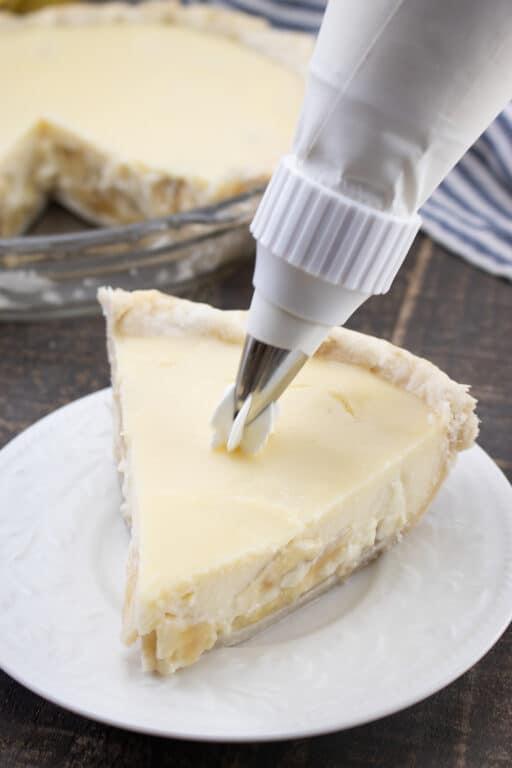 piping whipped cream on top of banana cream pie