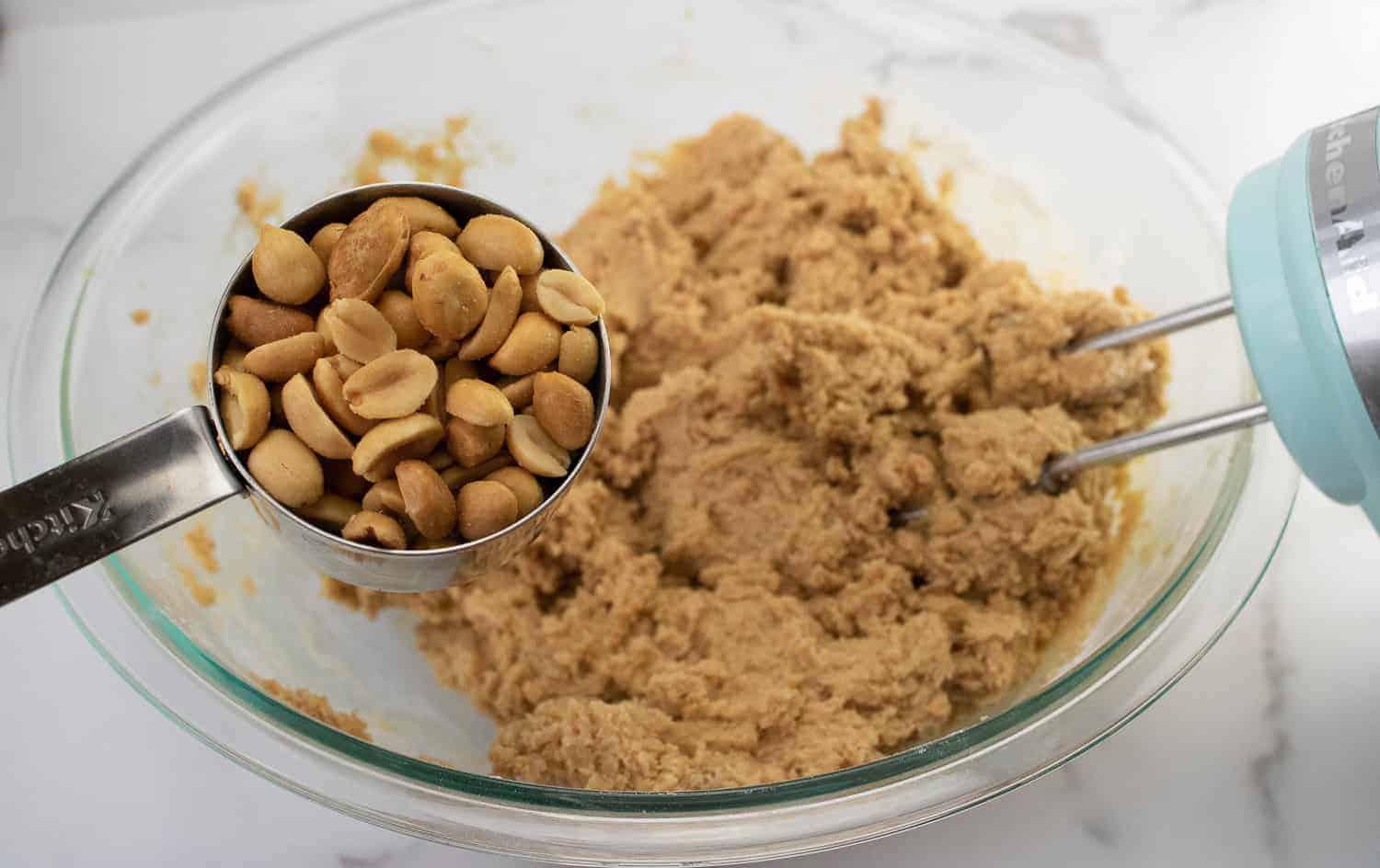 adding peanuts to peanut butter cookie dough