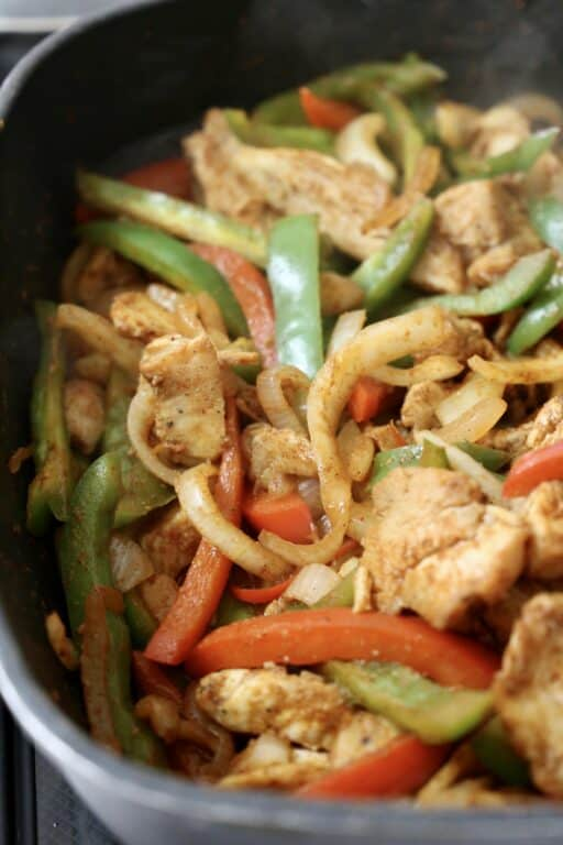 skillet with fajitas made with chicken, onions, and bell peppers