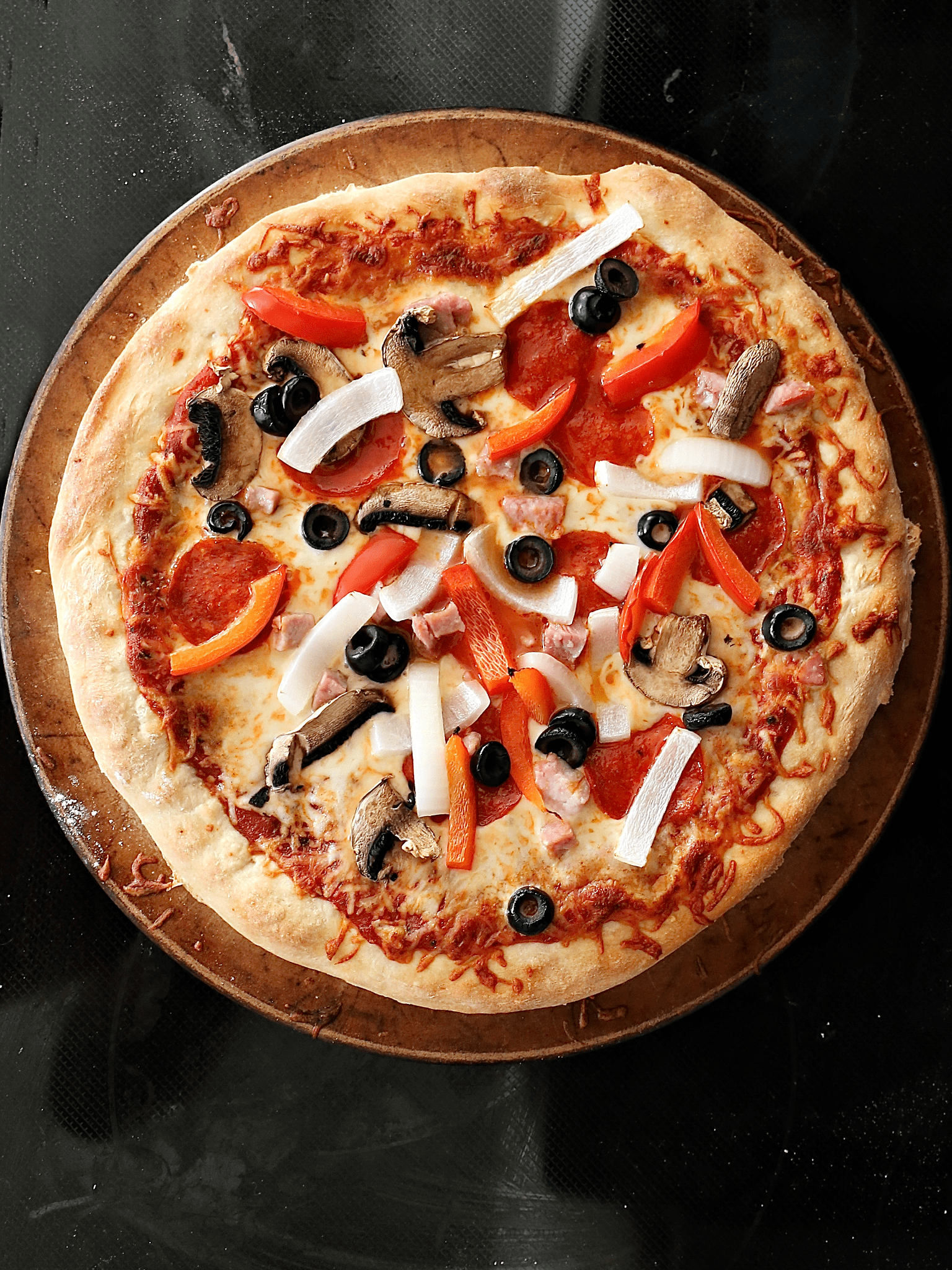 deluxe homemade pizza on a baking stone