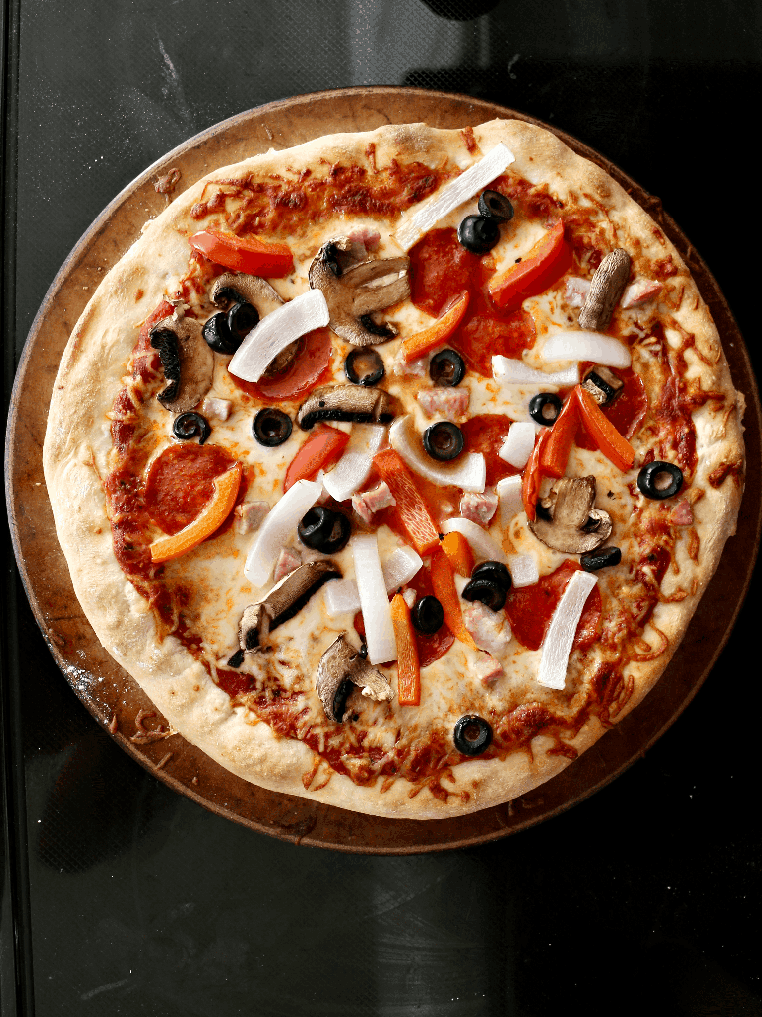 pizza with onions, bell peppers, olives, mushrooms, and pepperoni