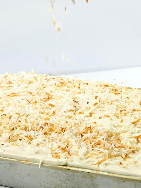 sprinkling coconut on a coconut sheet cake