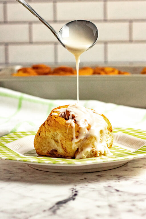 drizzling icing on top of a cinnamon roll