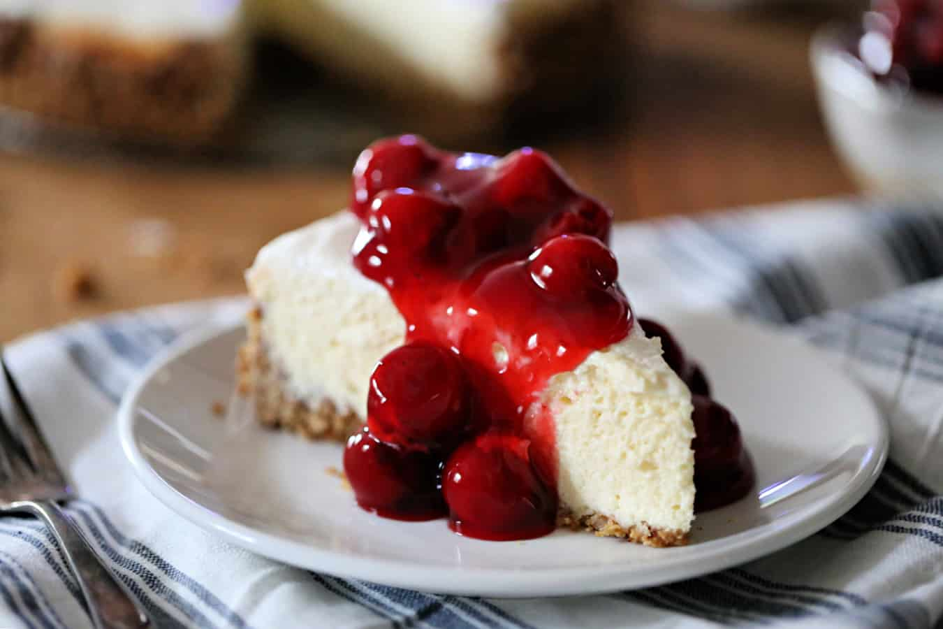 slice of baked cheesecake with cherries on top