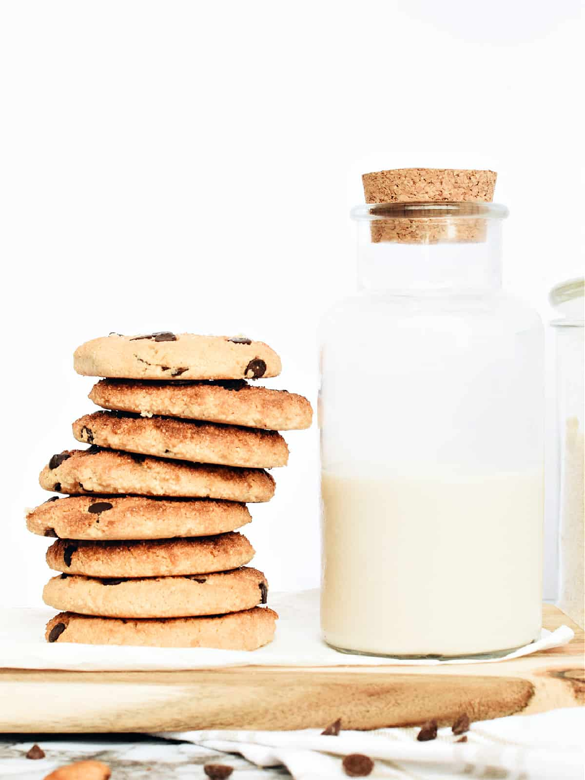 stack of almond cookies and bottle of milk