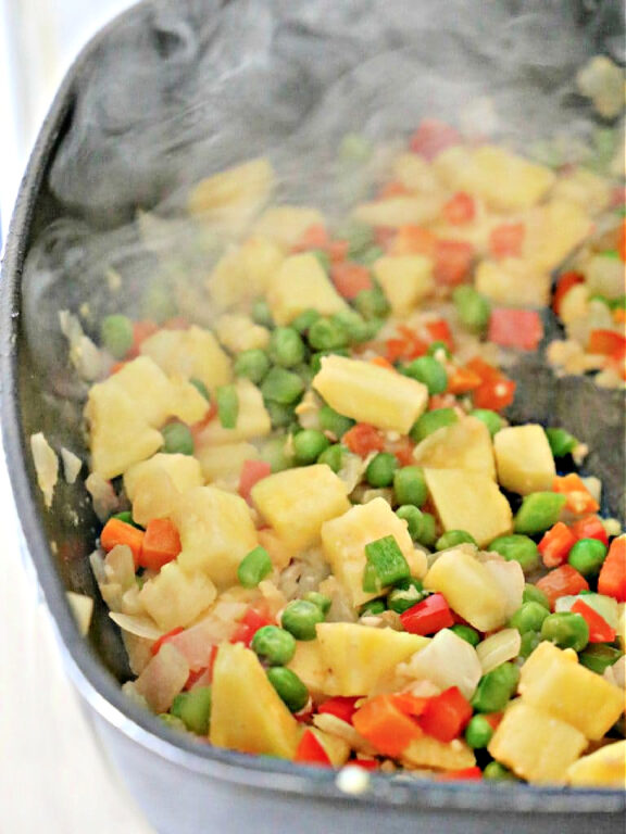 pineapple and vegetables being stir-fried