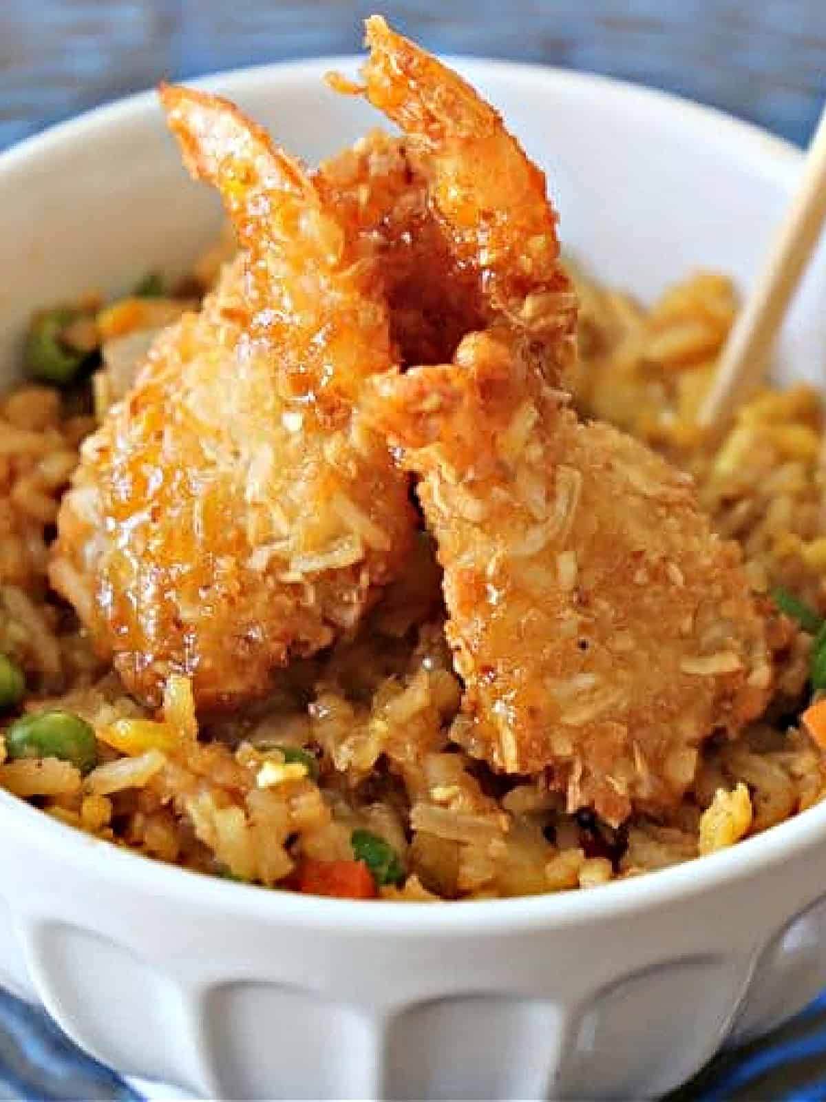 bowl of tropical fried rice topped with coconut shrimp