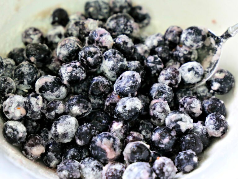 blueberries tossed in flour and sugar in a bowl