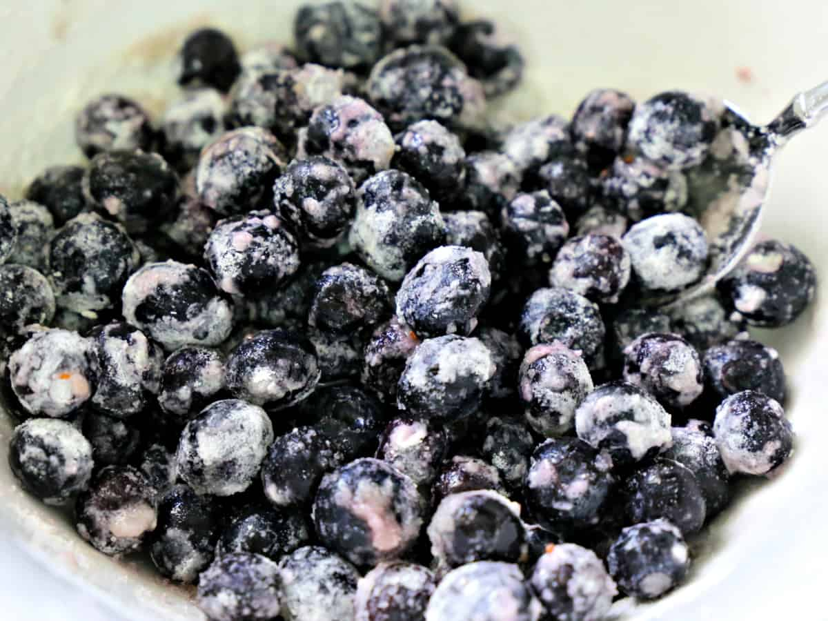 Blueberries tossed in flour and sugar in a bowl.