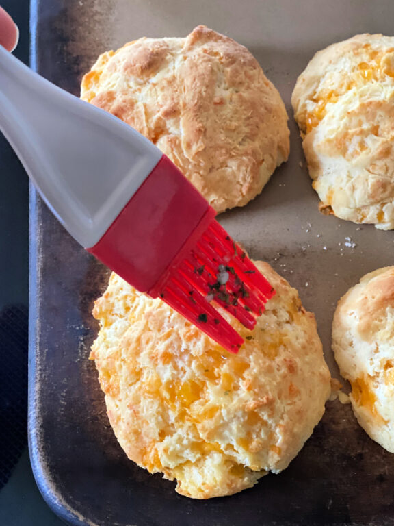 brushing cheddar biscuits with butter and herbs