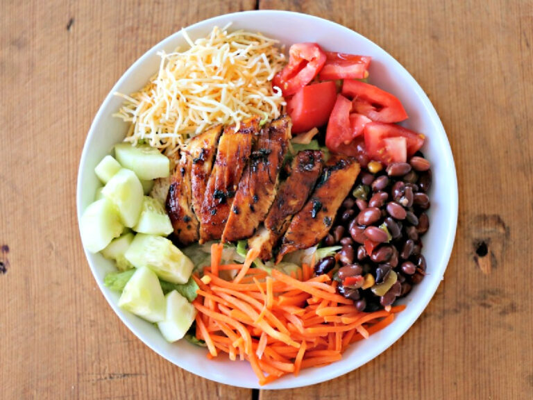 bowl of salad with chicken, carrots, cheese, and beans