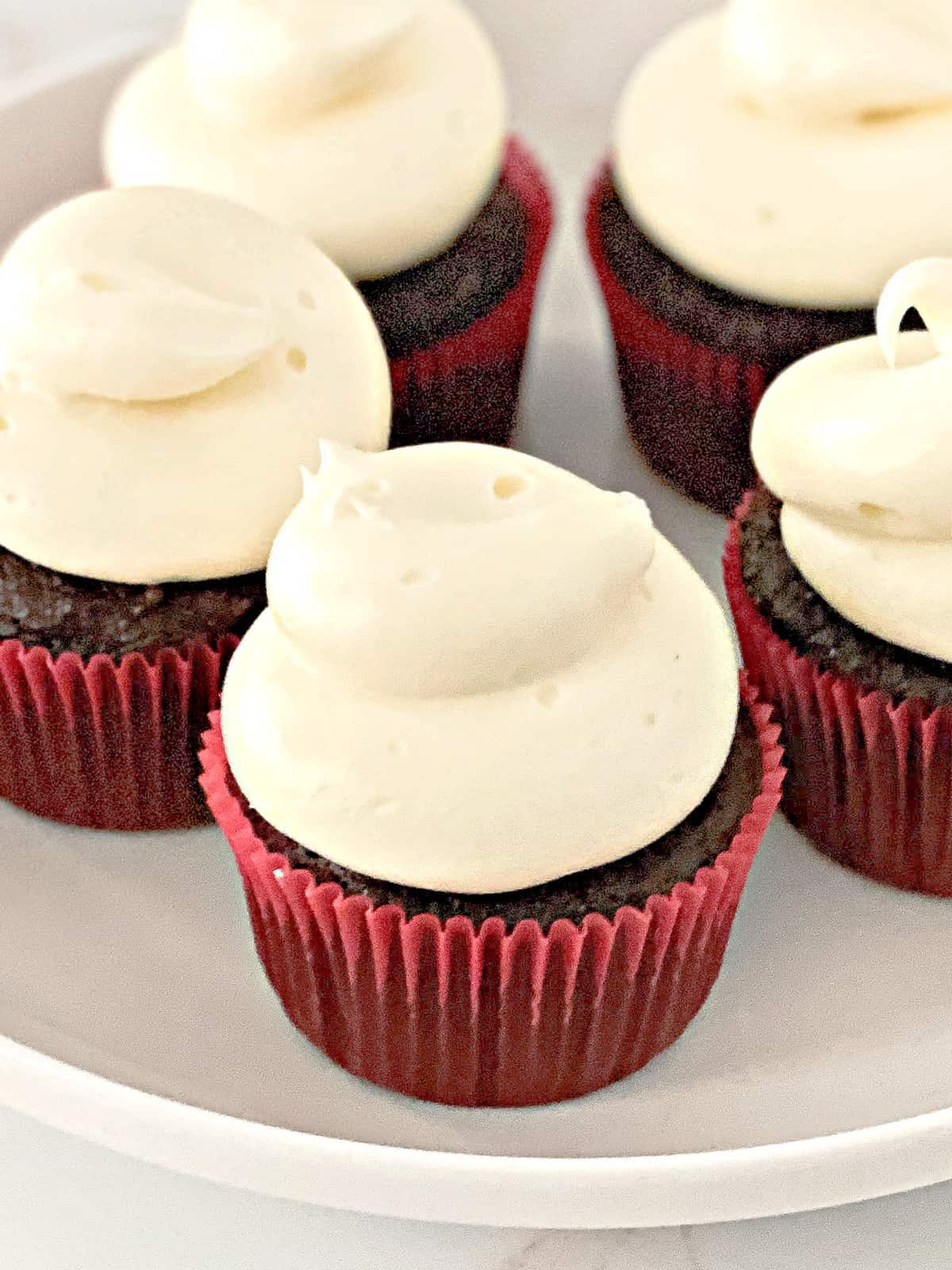 chocolate cupcakes decorated with cream cheese frosting on a plate