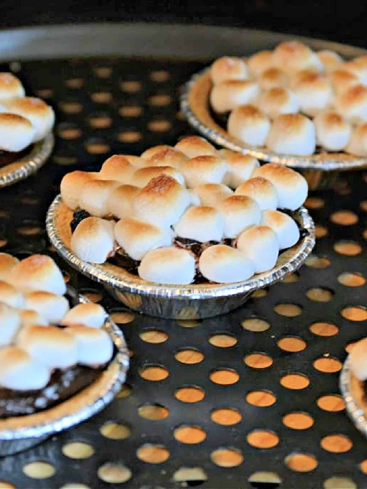 toasting marshmallows on top of a chocolate pie