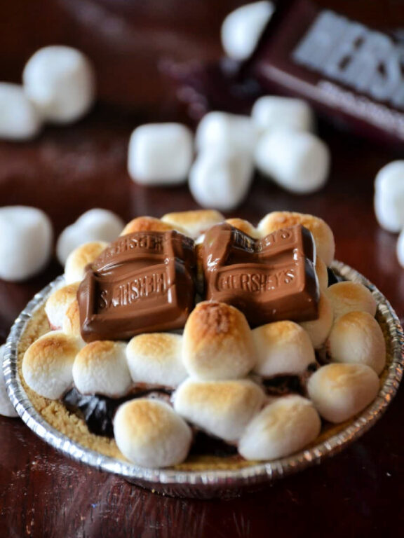 miniature s'mores pie made with a graham cracker crust, chocolate pudding, and topped with miniature marshmallows and a chocolate bar