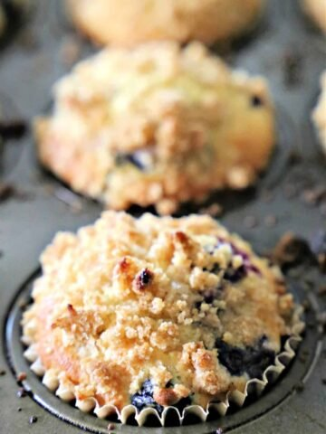 Blueberry muffins with crumb topping in a muffin pan.