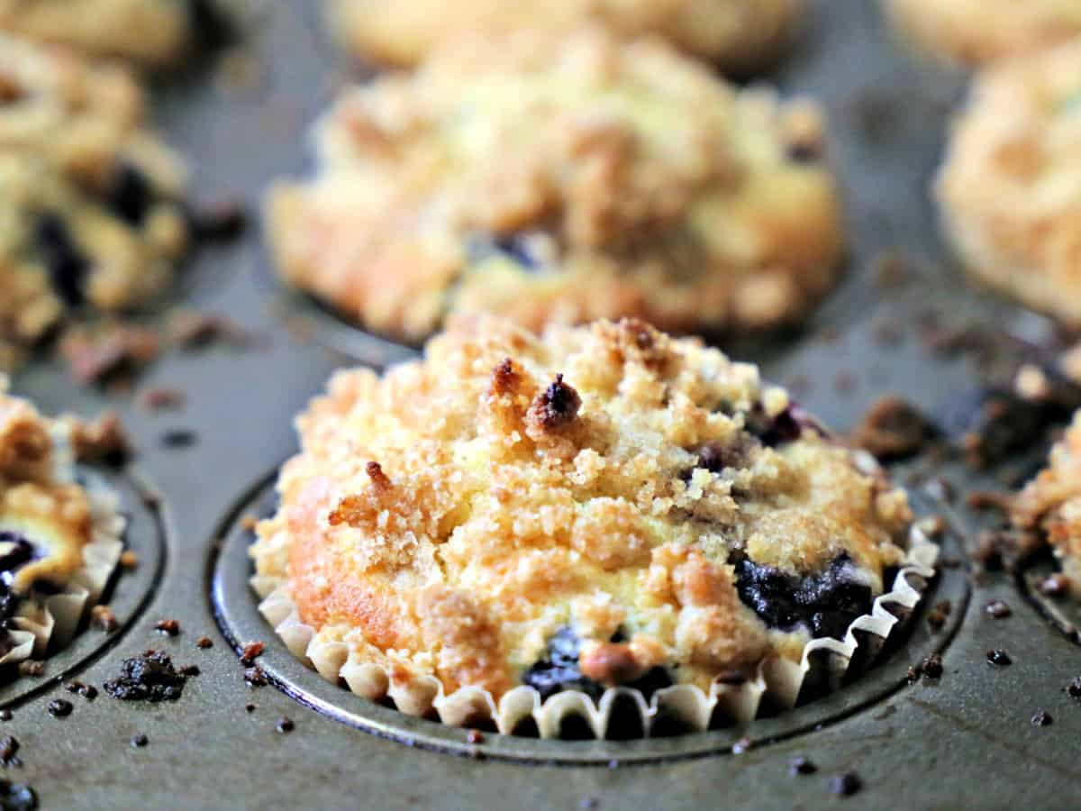 Blueberry muffins with crumb topping in a muffin tin.