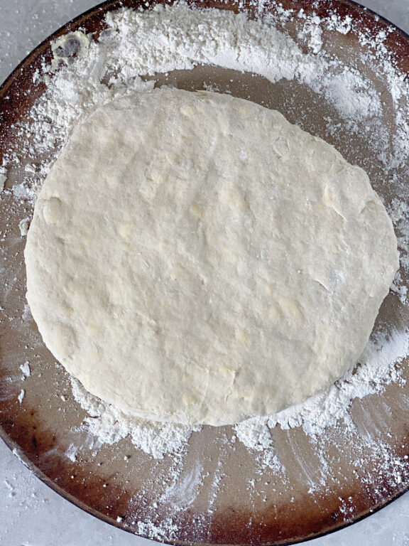 biscuit dough patted out on a baking stone