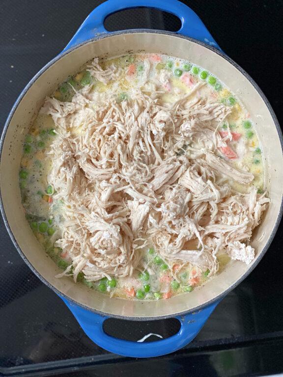 shredded chicken being added to chicken pot pie fillings
