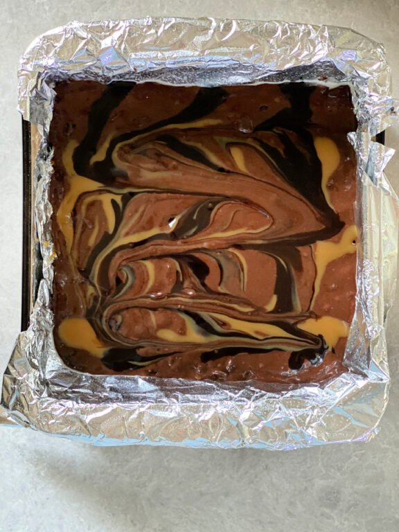 swirled brownie batter in a baking pan
