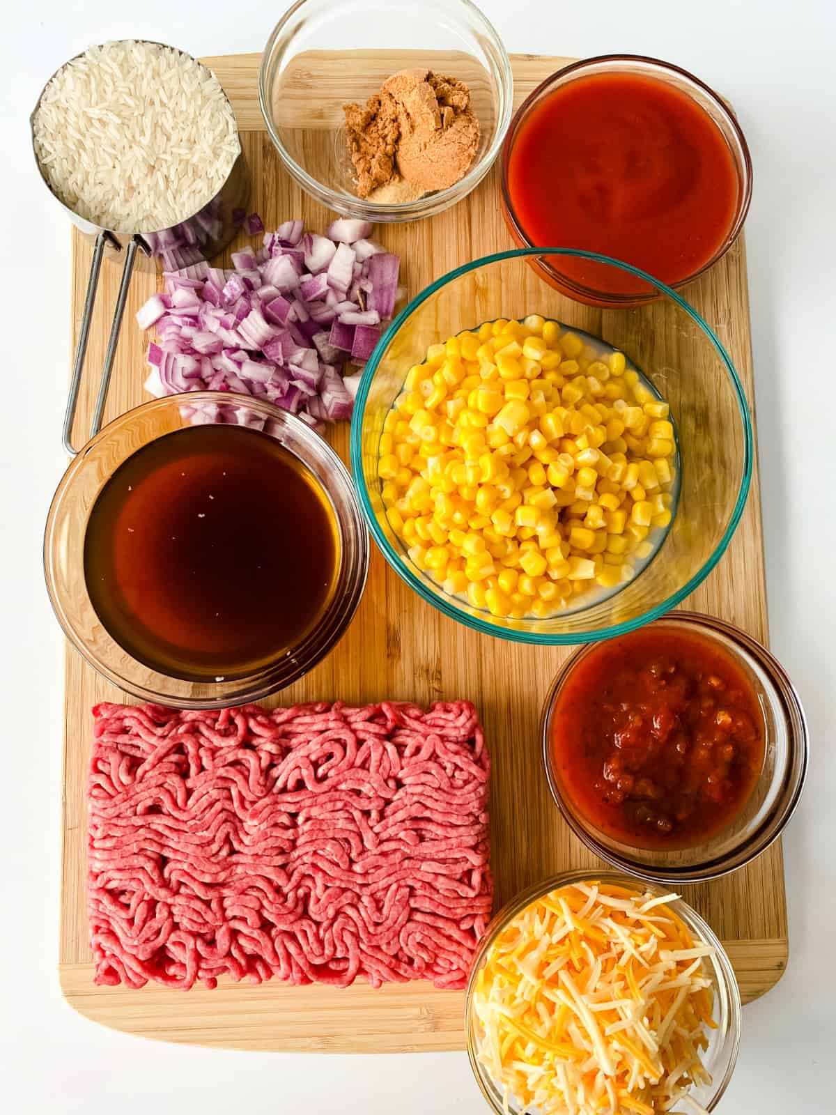 Ground beef, beef broth, red onion, corn, rice, cheese, salsa, and seasonings on a wooden cutting board.