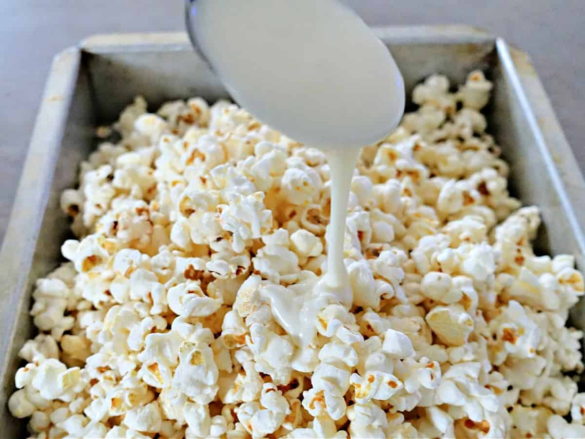 pouring almond bark on top of pop corn