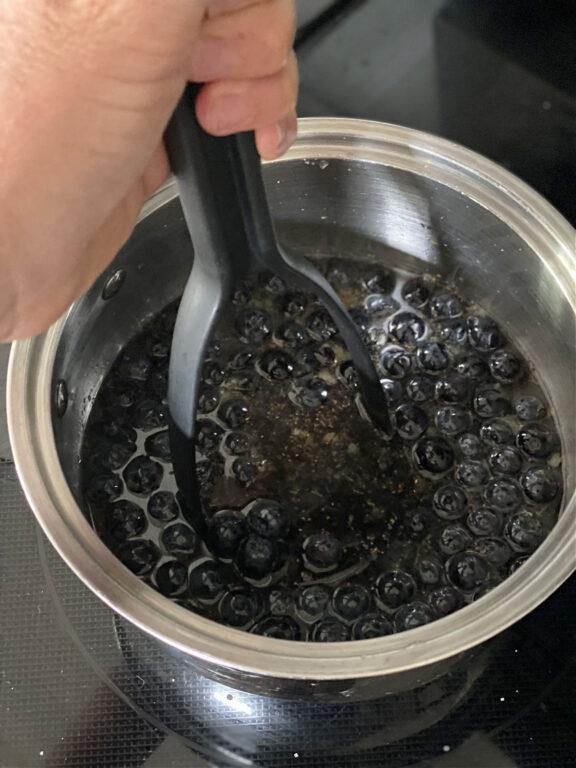 mashing blueberries in a pan