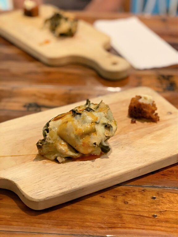 oyster Rockefeller and piece of fried cornbread