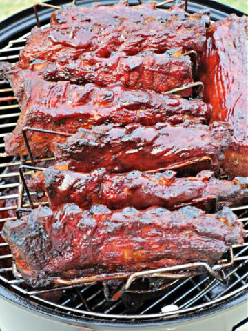 Smoker with slabs of ribs slathered with barbecue sauce.